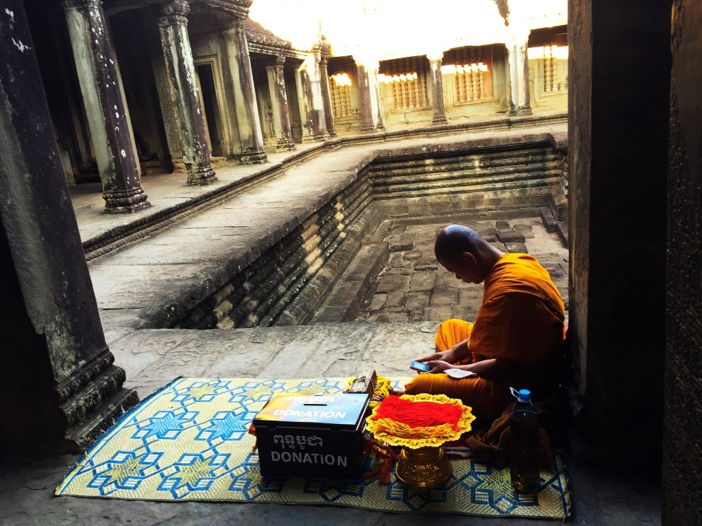 A monk at Angkor Wat, keeping up with the times.